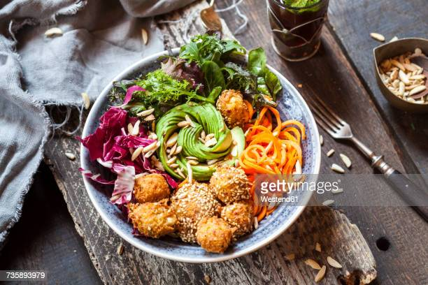 Rainbow salad bowl with carrots, lettuce, avocado, millet falafel and Moroccan mint tea