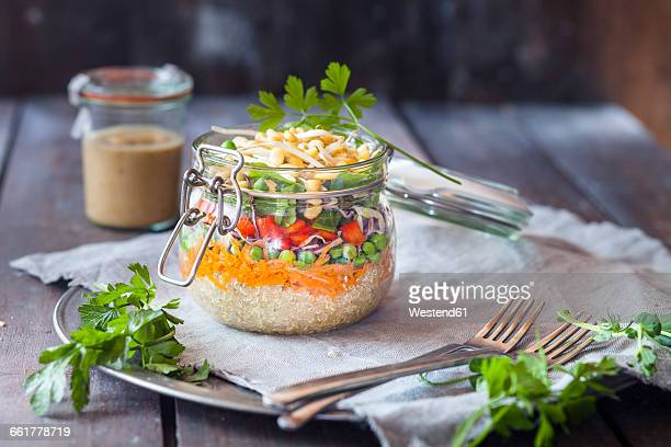 Rainbow salad in a jar, quinoa, carrots, peas, red cabbage, bell pepper, mung bean sprouts, dressing aside