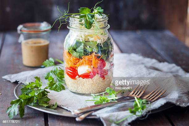 rainbow salad in a jar, quinoa, tomatoes, mozzarella, spinach, pea sprouts, dressing aside - jars with salad stock pictures, royalty-free photos & images