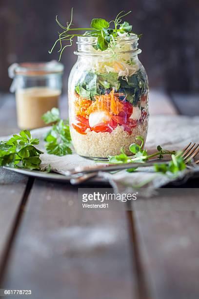 Rainbow salad in a jar, quinoa, tomatoes, mozzarella, spinach, pea sprouts