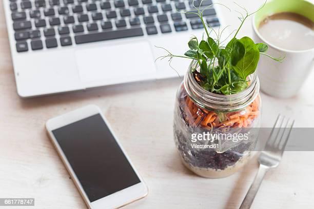 Rainbow salad in jar, smartphone, mug of coffee and laptop