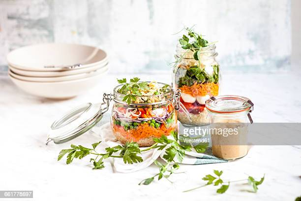 Rainbow salads in jars, quinoa, carrots, peas, red cabbage, bell pepper, mung bean sprouts, the other with tomatoes, mozzarella, spinach, pea sprouts, dressing aside