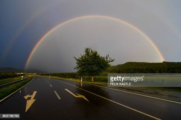 Rainbow spans over a street near Bodman, southern Germany, on June 29, 2017. / AFP PHOTO / dpa / Felix Kästle / Germany OUT