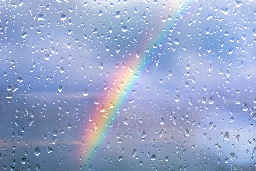 Rainbow through a window with drops after storm 918954002