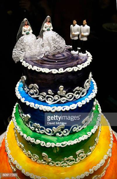 A rainbowcolored wedding cake is topped with male and female samesex couple figurines at a symbolic mass gay wedding celebrated by more than 100...