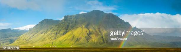 rainbows and sunlight illuminating remote mountain farms panorama iceland - lava plain stock pictures, royalty-free photos & images