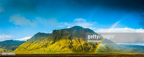 Rainbows over green mountain rural farmland pasture panorama Iceland
