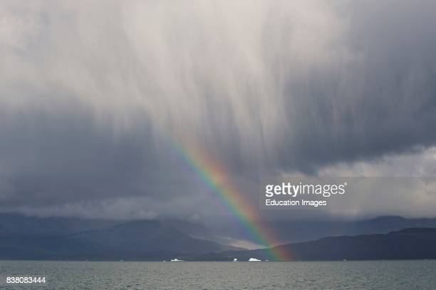 Rainclouds and rainbow over a broad fjord with icebergs in Southern Greenland close to Qaqortoq