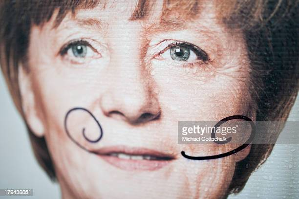 Raindrops and a mustache are seen on a election poster with a photo of German chancellor Angela Merkel on September 03 2013 in Finsterwalde Germany...