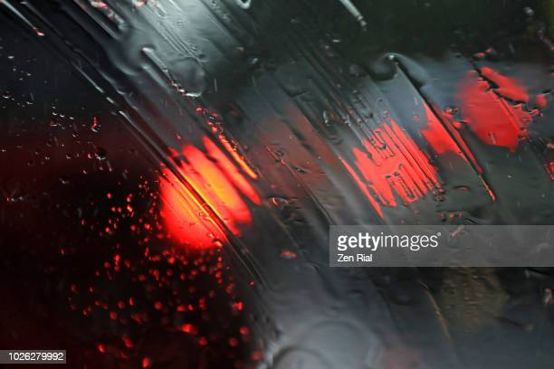 Raindrops and traffic lights seen through windshield during heavy rain