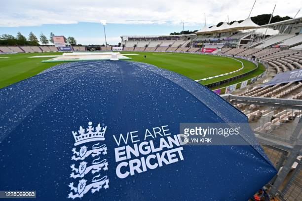 Raindrops cover an England umbrella in the empty stands as a patch of blue sky appears after play is abandoned for the day on the fourth day of the...