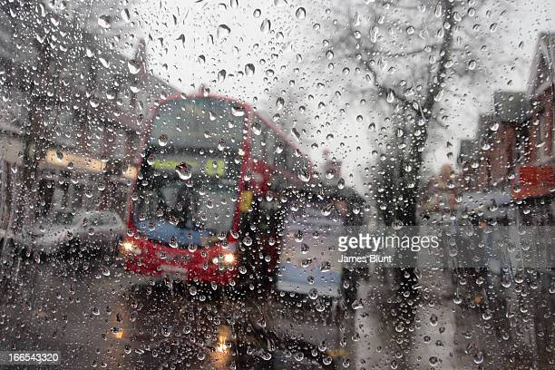 Raindrops on a transparent surface, with an out-of-focus background. Awful british weather in this outdoor scene with torrential rain. A red London...