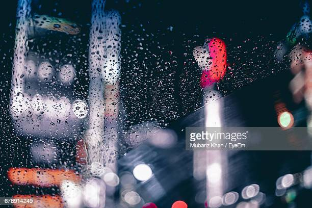 Raindrops On Car Windshield Against Illuminated Buildings At Night