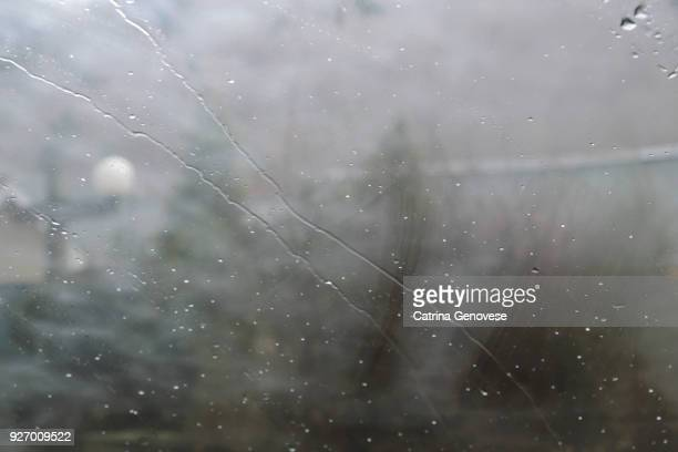 raindrops on car windshield with abstract view of rural scene containing trees and home exterior - raindrop stock pictures, royalty-free photos & images