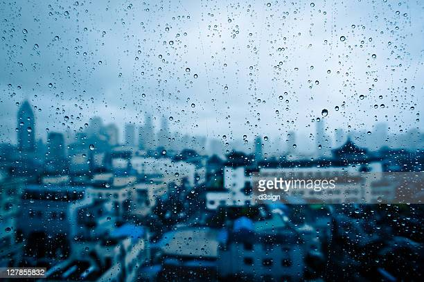 Raindrops on window glass with cityscape, China