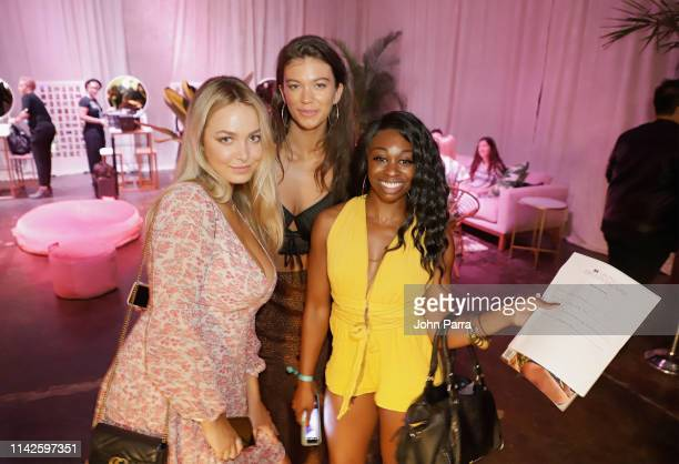 Raine Michaels and Erin Willerton pose with a guest at the Sports Illustrated Swimsuit On Location at Ice Palace on May 10 2019 in Miami Florida