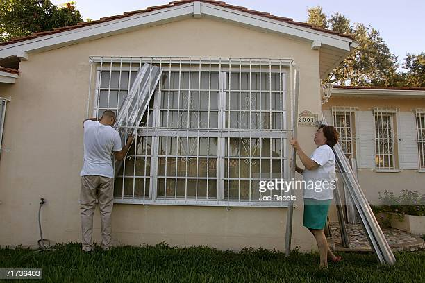 Rainel Gonzalez and Gina Scott put shutters over a window as they prepare their home for the approaching Tropical Storm Ernesto that is threatening...