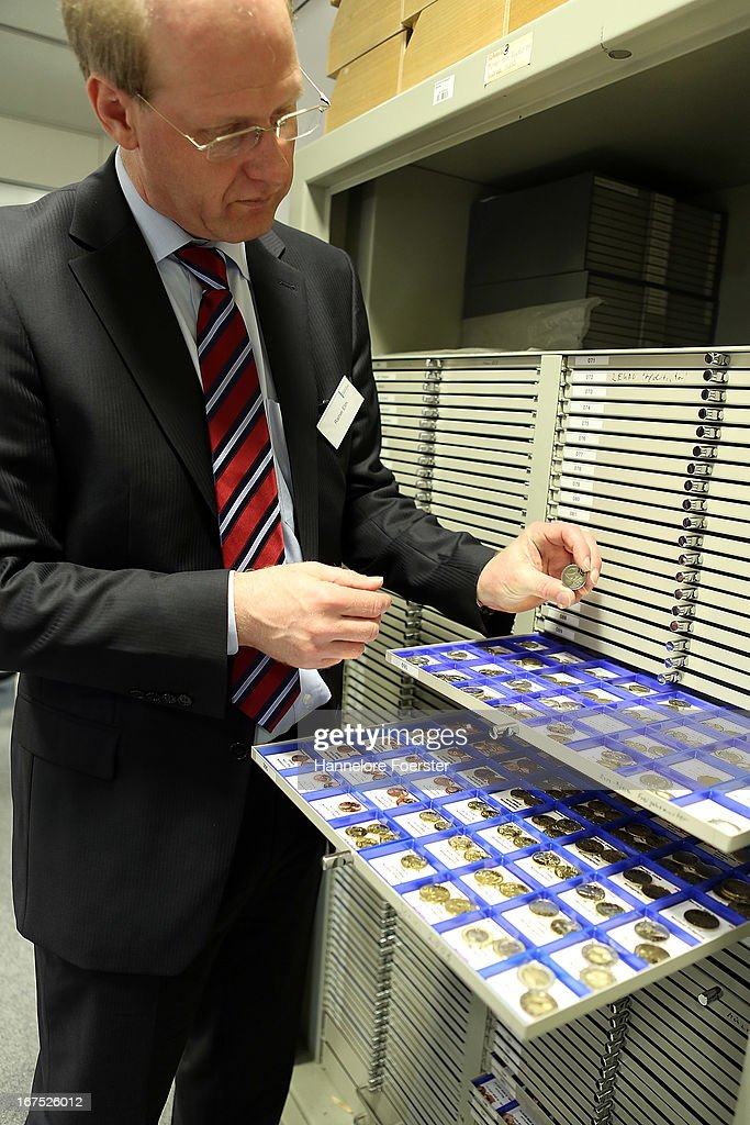 Rainer Elm, head of section, shows a coin collection, at the analysis lab (Nationales Analysezentrum fuer Falschgeld und beschaedigtes Bargeld) of the German Bundesbank during a demonstration for the media on April 26, 2013 in Mainz, Germany. The center is Germany's main facility for analysing potentially counterfeit money and also repairs damaged banknotes.