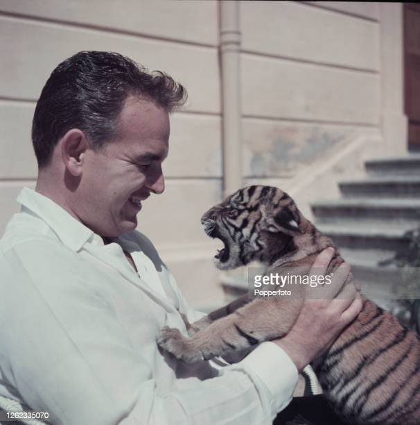 Rainier III, Prince of Monaco holds a 3 week old tiger cub, a gift from his close friend Emperor Bao Dai of Vietnam, at a residence in the...