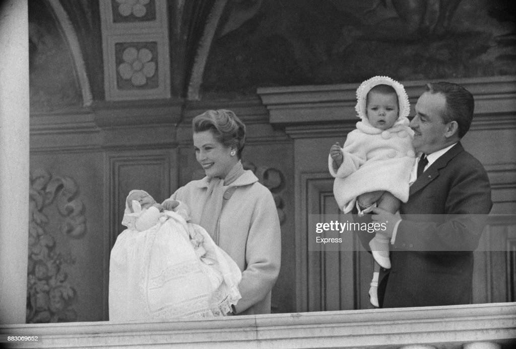 Rainier III, Prince of Monaco (1923 - 2005), holds Caroline, Princess of Hanover, while wife, American actress Grace Kelly, Princess of Monaco (1929 - 1982), presents Prince Albert II from the balcony of the Prince's Palace of Monaco, April 1958.