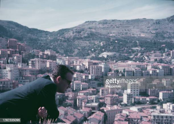 Rainier III, Prince of Monaco looks out from a balcony overlooking residential blocks built on Maritime Alps hillsides in the Principality of Monaco...