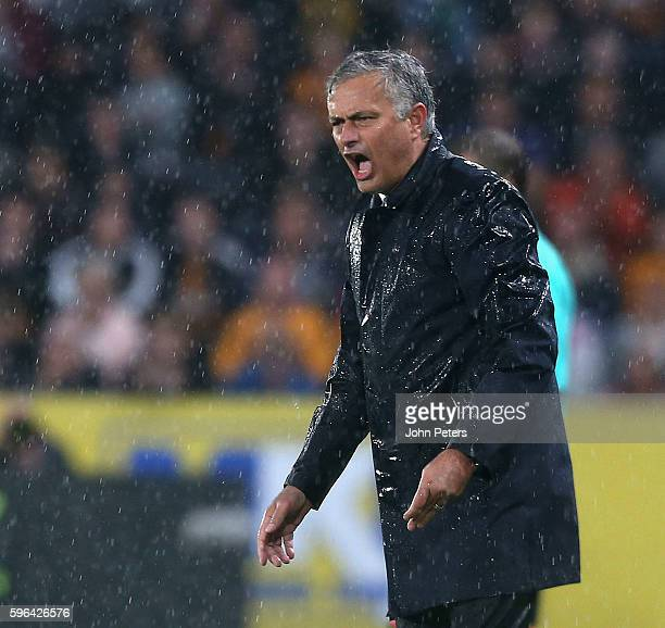 A rainsoaked Manager Jose Mourinho of Manchester United watches from the touchline during the Premier League match between Manchester United and Hull...
