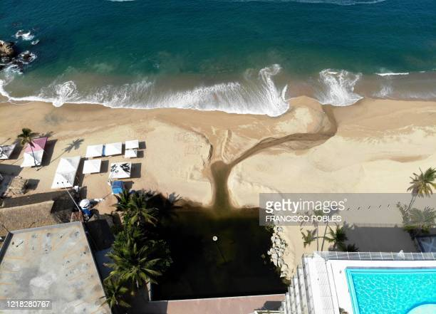 Rainwater carrying plastic pollution from the city runs into the Bay of Santa Lucia at a beach in Acapulco, in the Pacific coast of Mexico, on June...