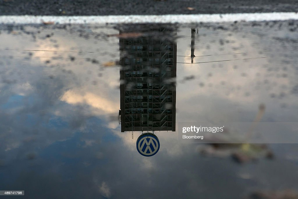 A rainwater puddle reflects a VW logo and above a building under construction at the Volkswagen AG headquarters in Wolfsburg, Germany, on Wednesday, Sept. 23, 2015. Volkswagen's escalating scandal over emissions-test cheating is beginning to ripple across the $10 trillion global corporate bond market. Photographer: Krisztian Bocsi/Bloomberg via Getty Images