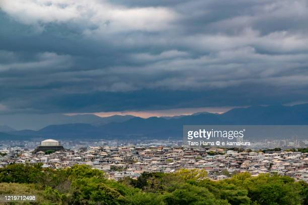 rainy clouds on the residential districts in kanagawa prefecture of japan - chigasaki stockfoto's en -beelden