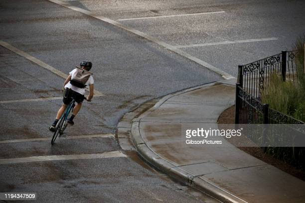 rainy day bicycle messenger - taking a corner stock pictures, royalty-free photos & images