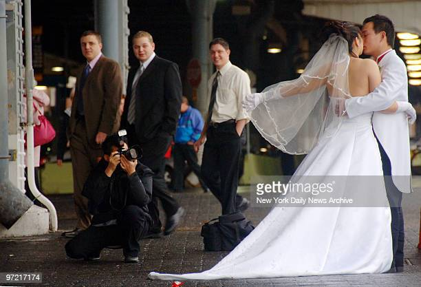 A rainy day isn't dampening the spirits of a bride and groom having wedding photos taken of them at the South Street Seaport as onlookers stroll by
