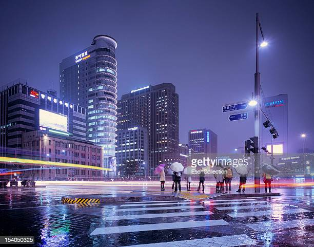 rainy evening with people waiting to cross street - korea stock pictures, royalty-free photos & images