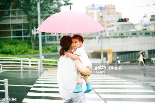 rainy in tokyo. - mother son shower stock photos and pictures