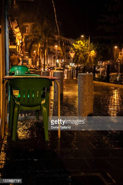 rainy street scene at night with some wet tables and chairs - dorte fjalland fotografías e imágenes de stock