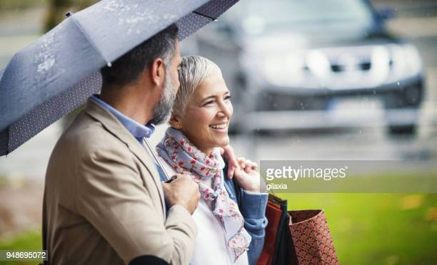 rainy walk home from shopping. - umbrella stock pictures, royalty-free photos & images