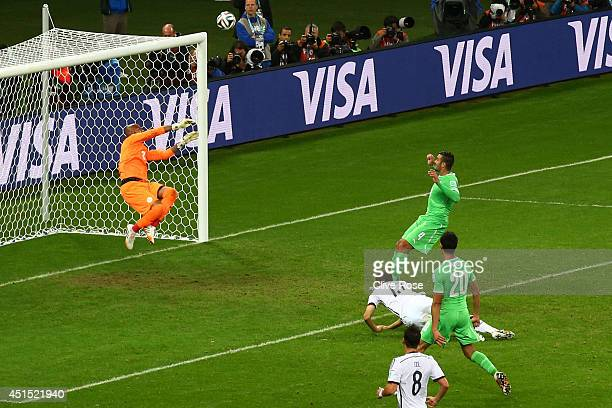 Rais M'Bolhi of Algeria saves a header on goal by Thomas Mueller of Germany during the 2014 FIFA World Cup Brazil Round of 16 match between Germany...
