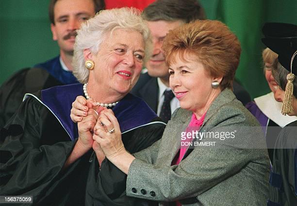 Raisa Gorbachev , wife of Soviet President Mikhail Gorbachev, raises the hands of Barbara Bush , wife of US President George Bush 01 June 1990 while...