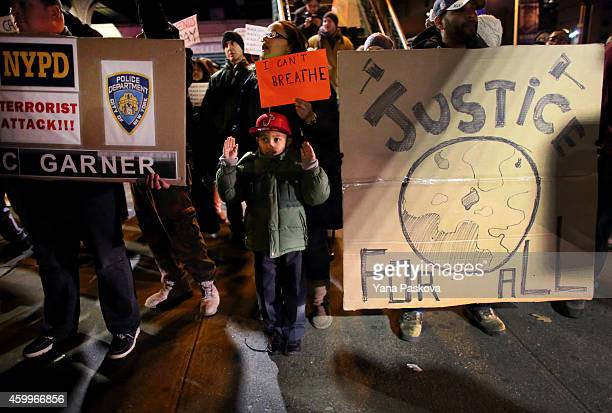 Raisa Valerio and her son Tyler Valerio join a group on E 125th St during a protest December 4 2014 in New York City Protests began after a Grand...