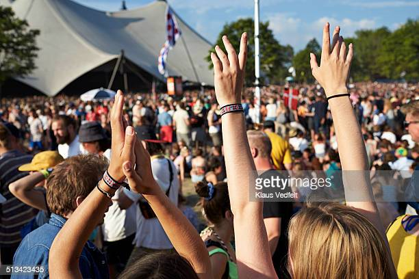 Raised clapping hands at concert with big crowd