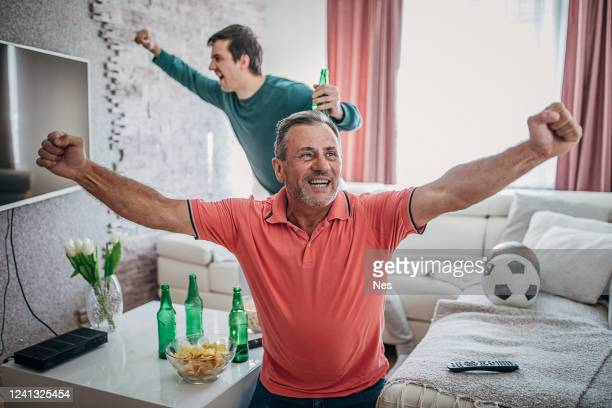 raised hands of fans in front of the tv - fan enthusiast stock pictures, royalty-free photos & images