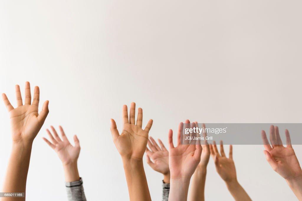 Raised hands of women : Stock Photo