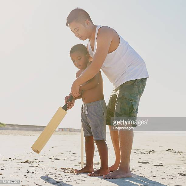 raising a future cricket star - beach cricket stock pictures, royalty-free photos & images