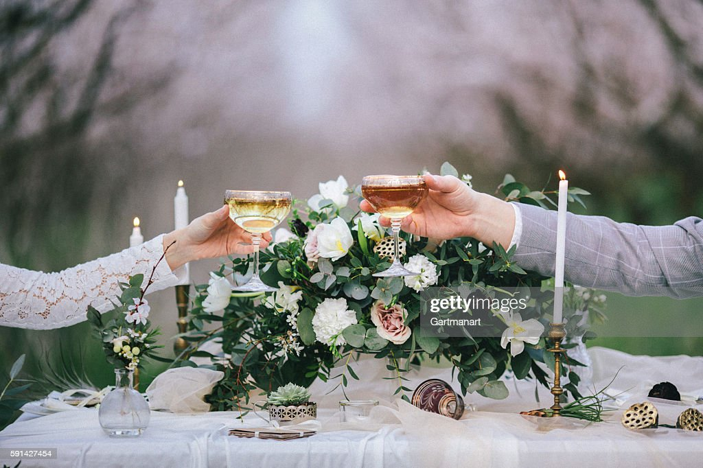 Raising glasses with champagne at the wedding table : Stock Photo