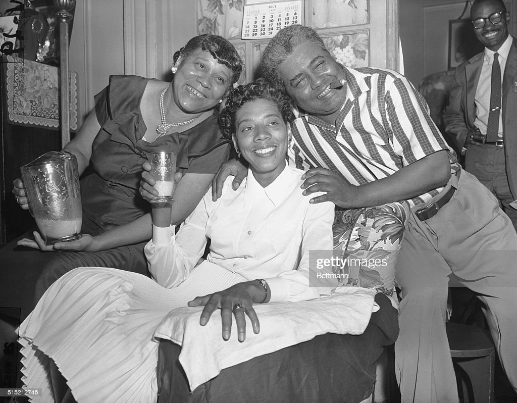 Raising her glass of milk in a toast, Althea Gibson, the new women's Wimbledon singles champion, shows she's glad to be home, as her proud parents, Annie and Daniel Gibson, stand by at the Gibson home. Althea, the first African American to ever win a Wimbledon singles title, received a hero's welcome on her arrival in Manhattan.