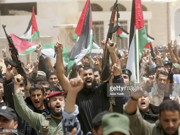Raising their fingers while holding their guns and national flags Palestinian members of the security forces shout slogans as they rally in support...