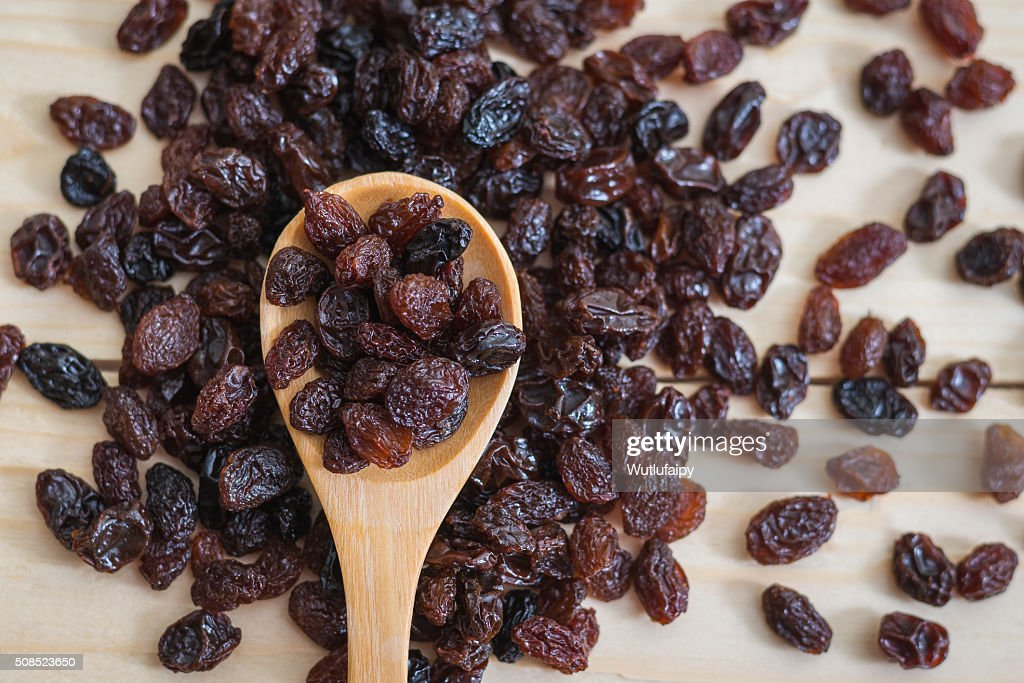 Raisins in a wooden spoon : Stock Photo