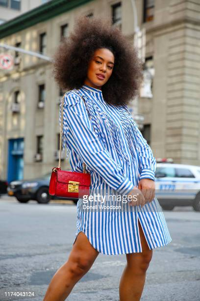 Raissa Santana arrives at the Libertine show at Spring Studios for New York Fashion Week wearing a blue and white dress with a red purse on September...