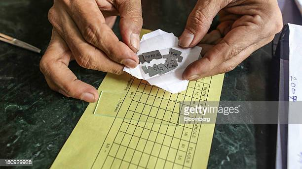 D V Raja a paramedical worker for the Bombay Leprosy Project holds pieces of broken razor blades used for skin smear tests for a photograph at the...