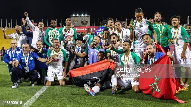 Raja Casablanca's players pose for a group picture with their respective national flags as they celebrate winning the CAF Super Cup trophy after...