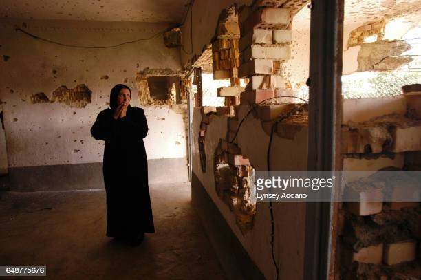 Raja Mohammed stands in her home allegedly destroyed by the Americans by tank fire in a night raid in which her husband was detained along with...